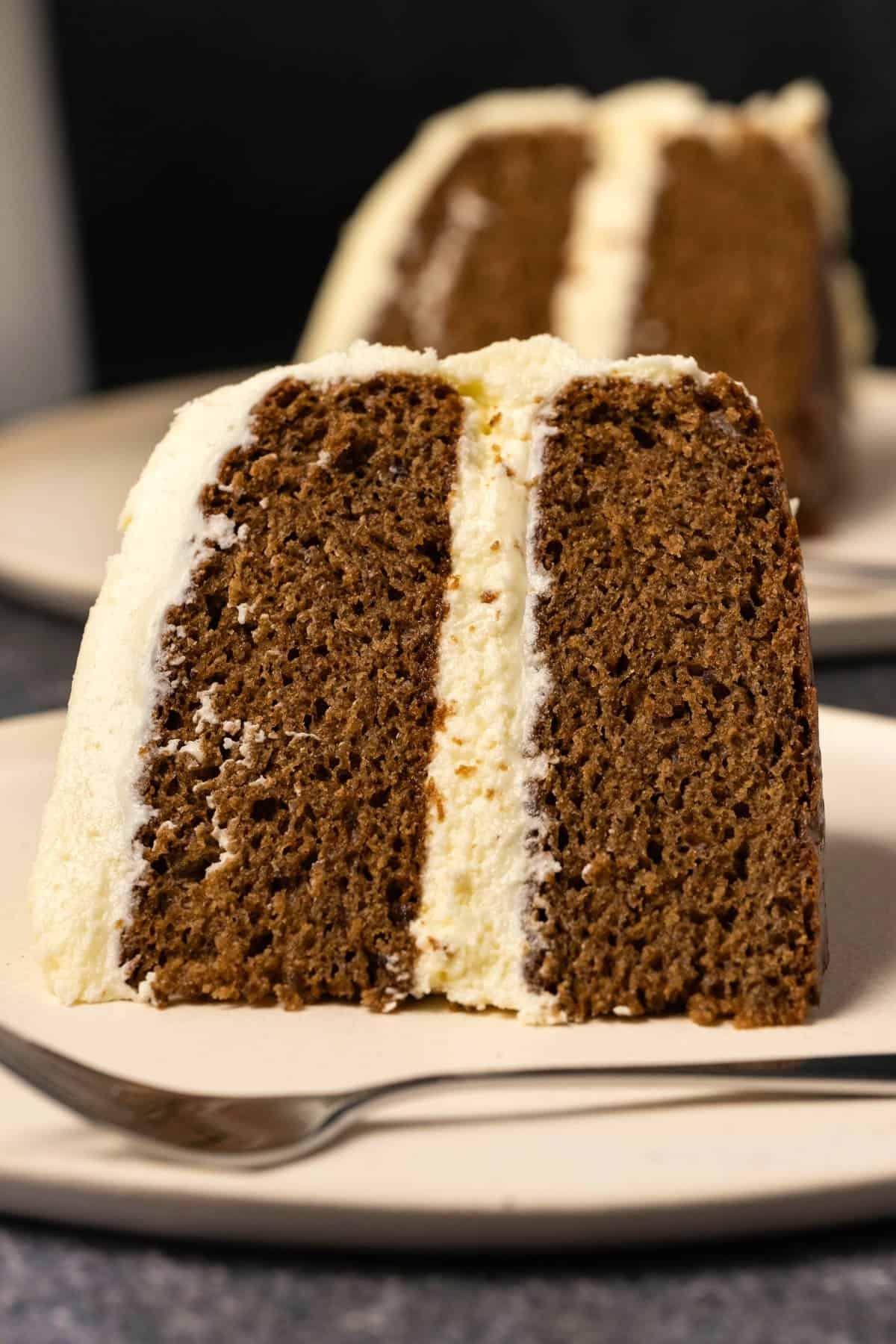 Slice of frosted vegan gingerbread cake on a white plate.