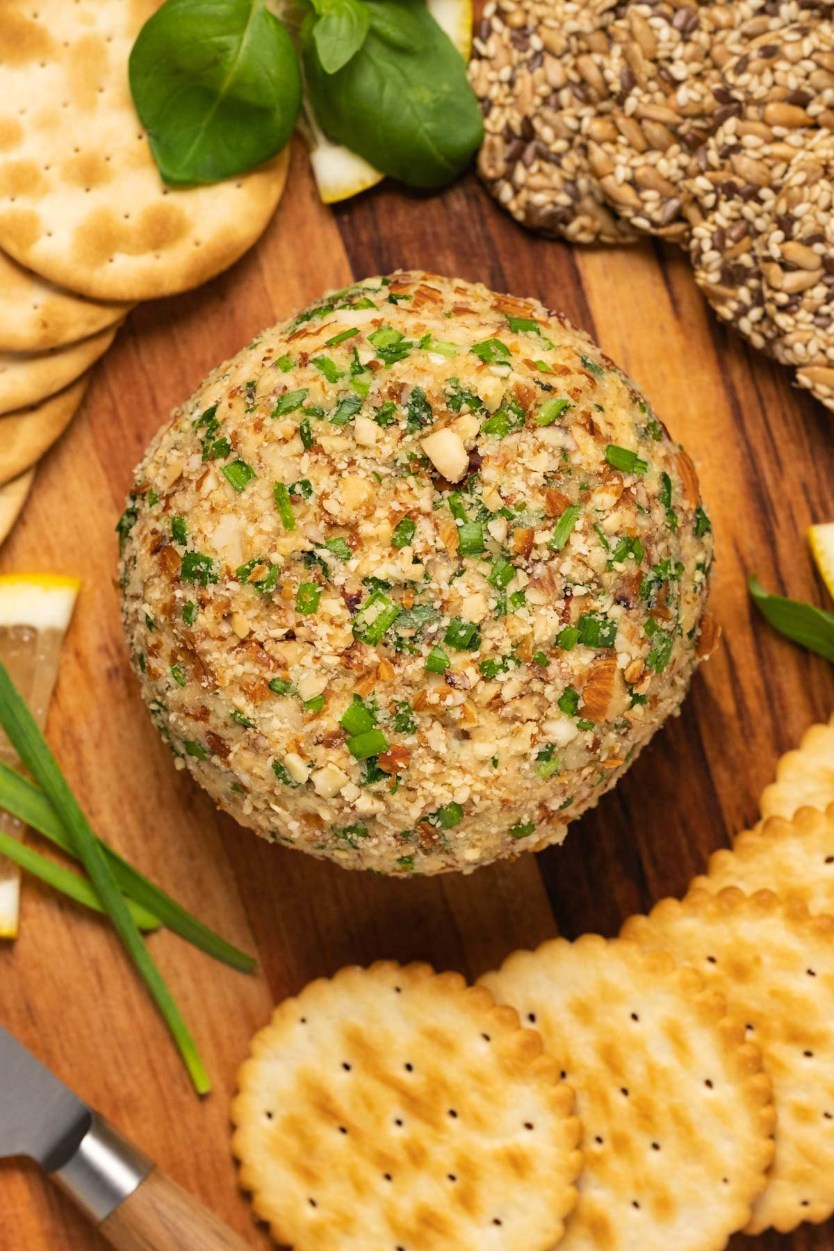 Vegan cheese ball with crackers and fresh basil on a wooden board.