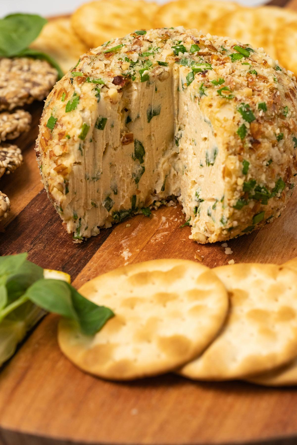 Cheese ball on a wooden board with crackers and fresh basil.