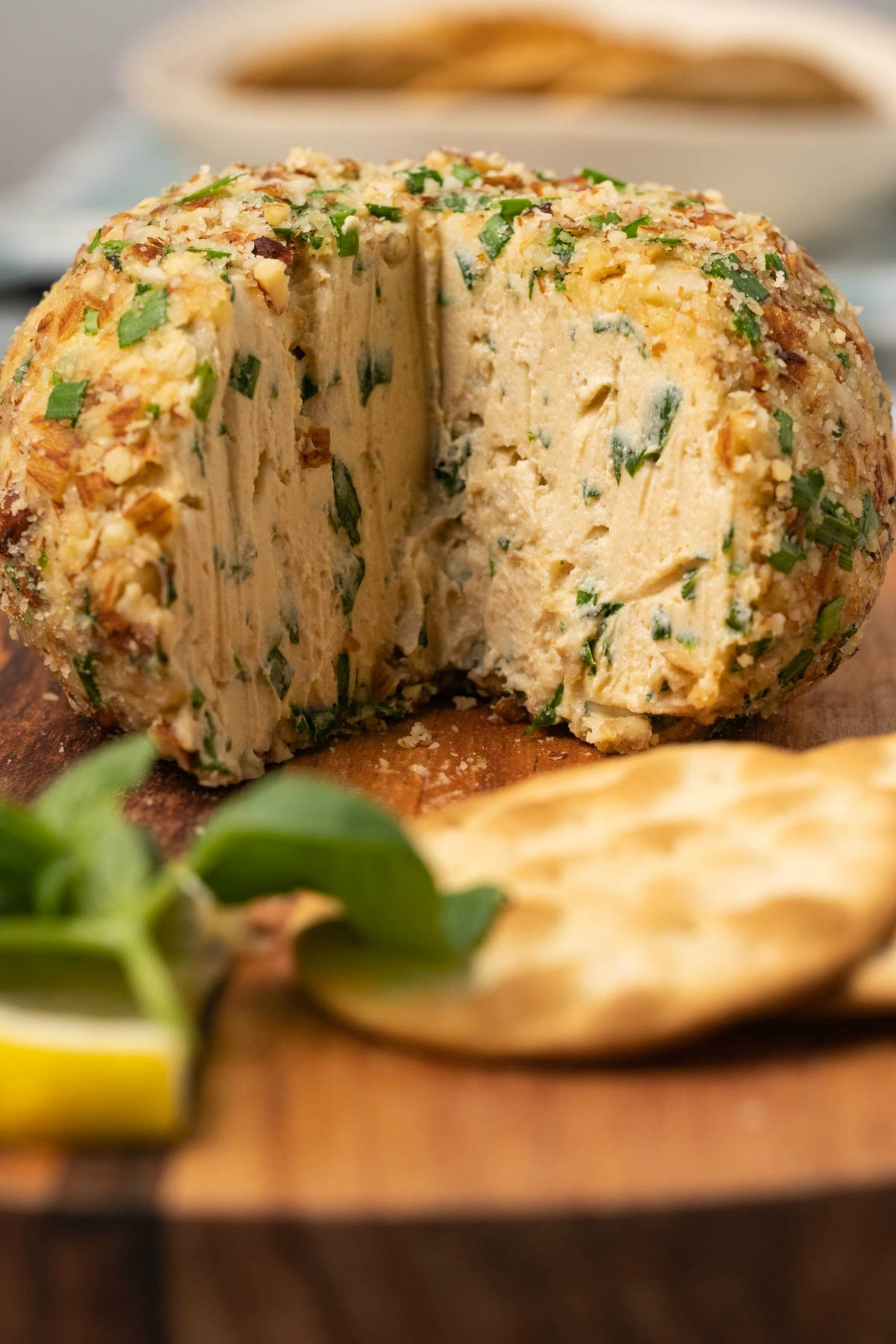 Cheese ball with crackers and basil on a wooden board.