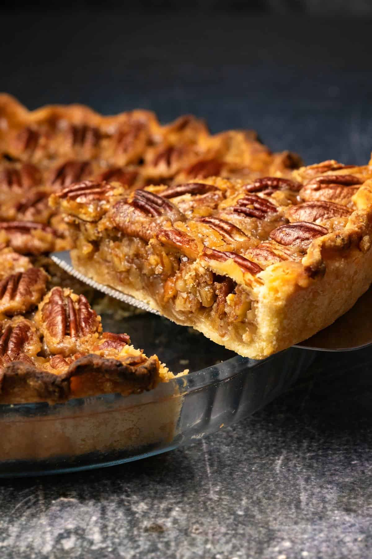Vegan pecan pie in a glass pie dish with one slice cut and ready to serve.