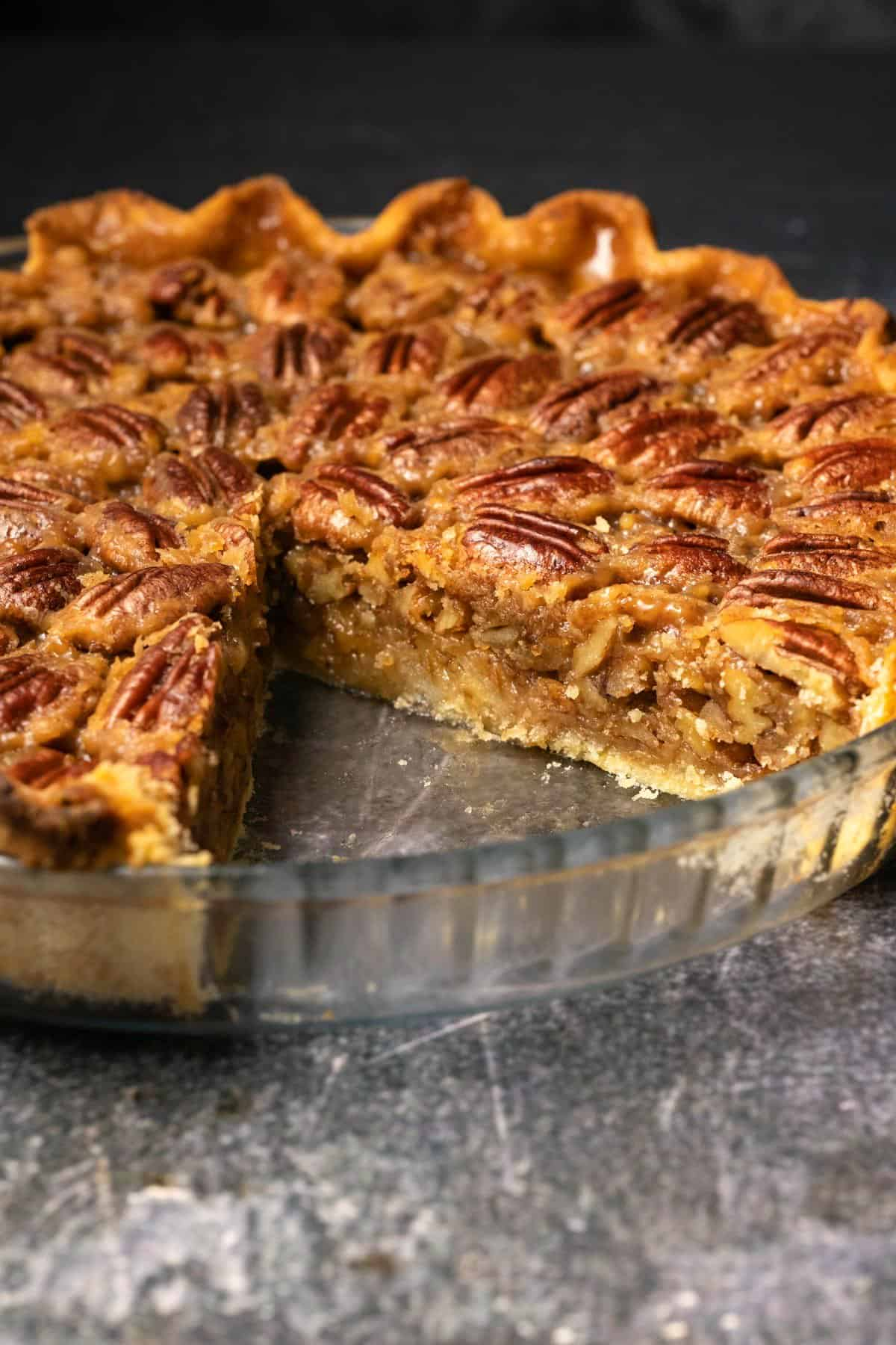 Vegan pecan pie in a glass dish with one slice missing.