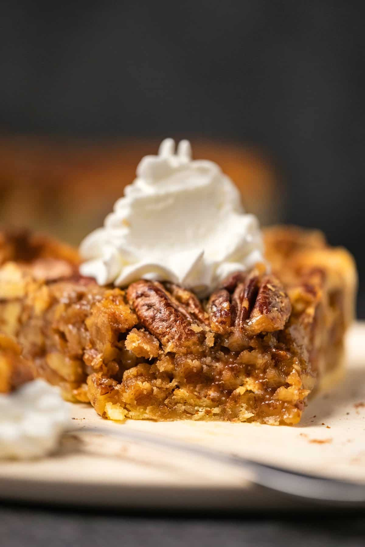 Slice of vegan pecan pie on a white plate with a cake fork.
