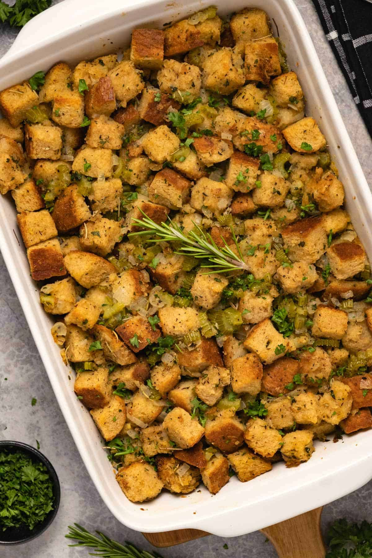 Vegan stuffing with fresh rosemary in a white dish.