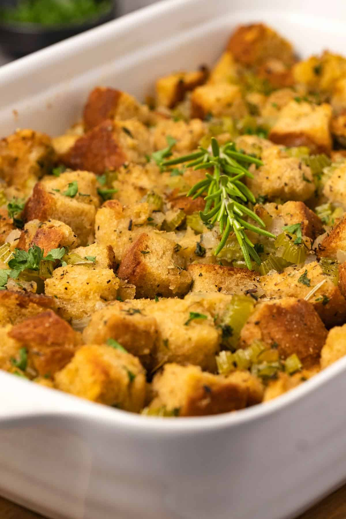 Stuffing with fresh rosemary and parsley in a white dish.