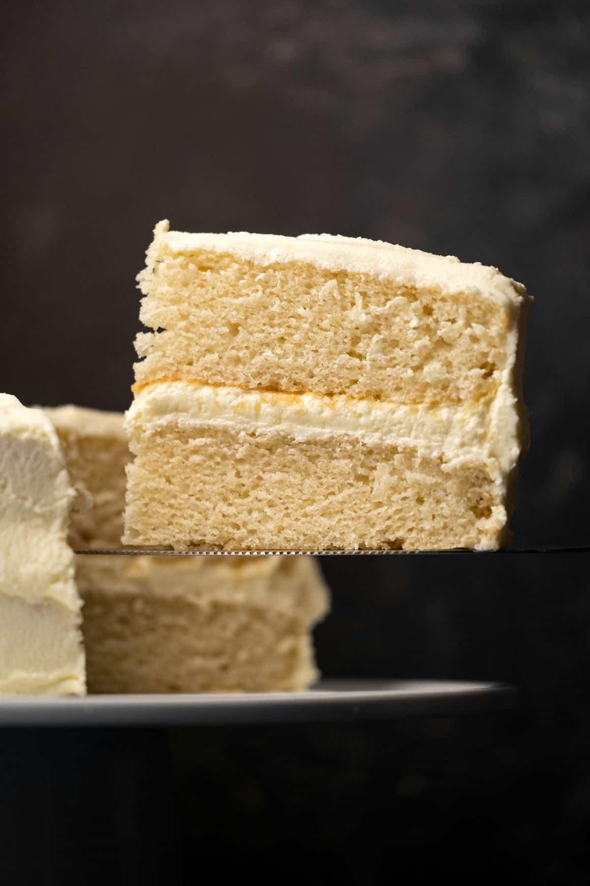 Slice of vegan white cake on a cake lifter.