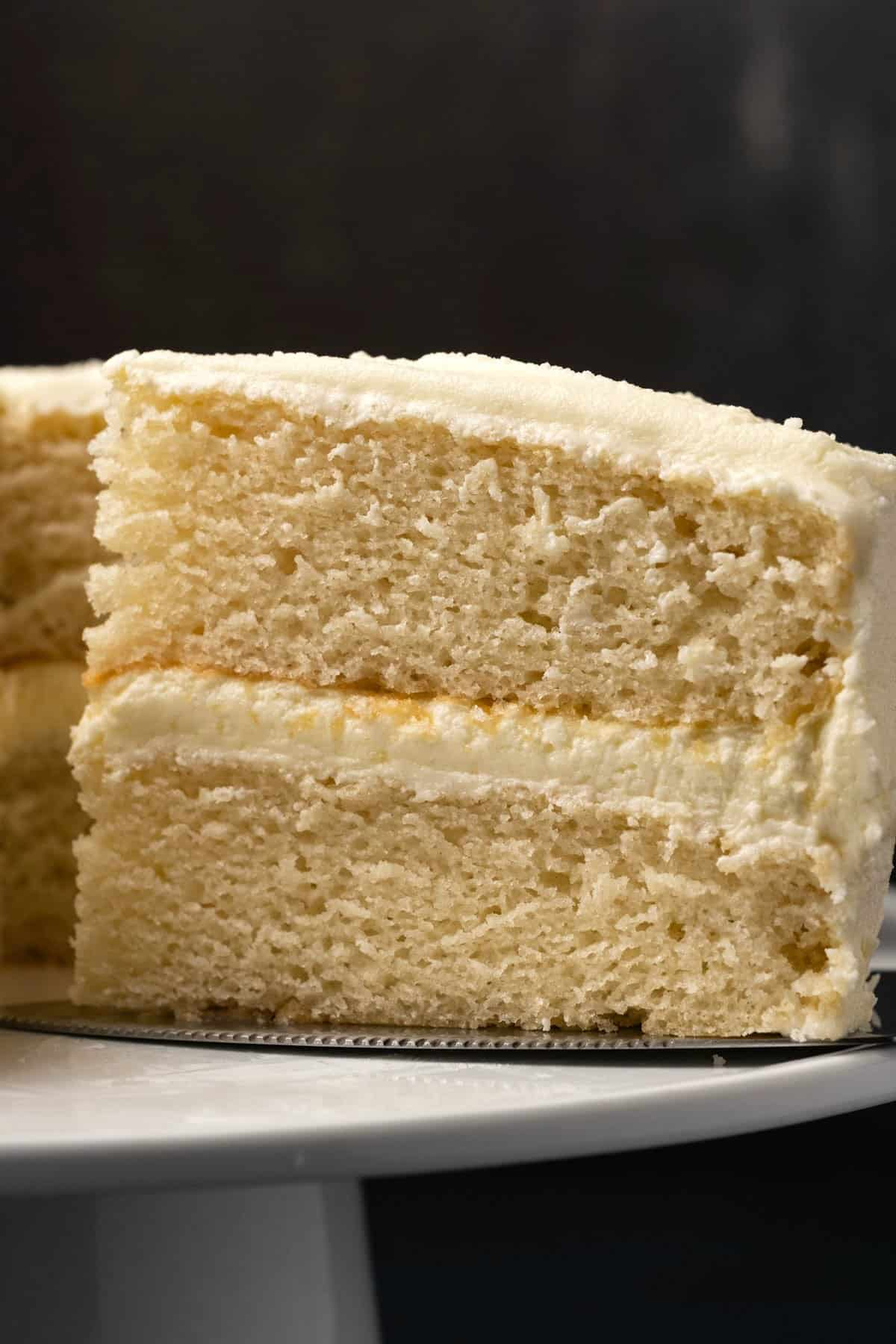 Vegan white cake with a slice cut on a white cake stand.