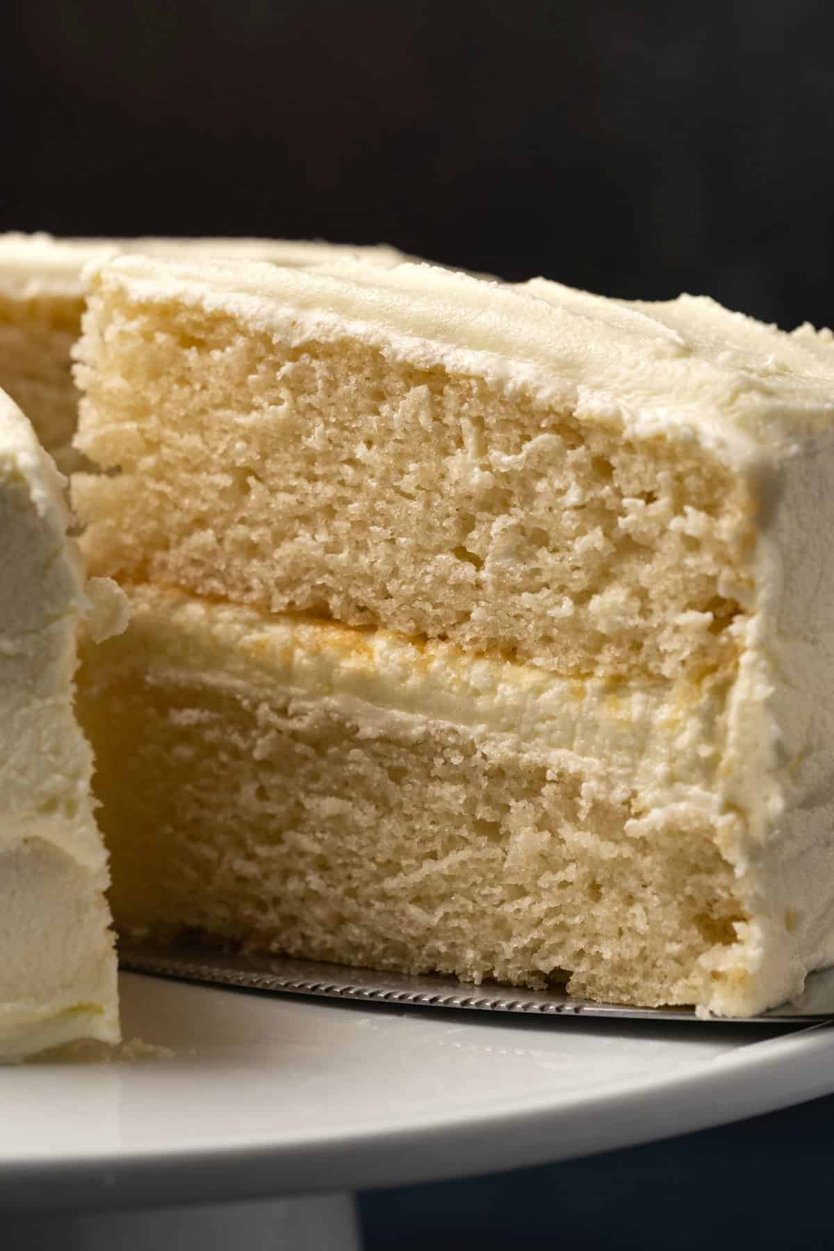 White cake with one slice cut on a white cake stand.