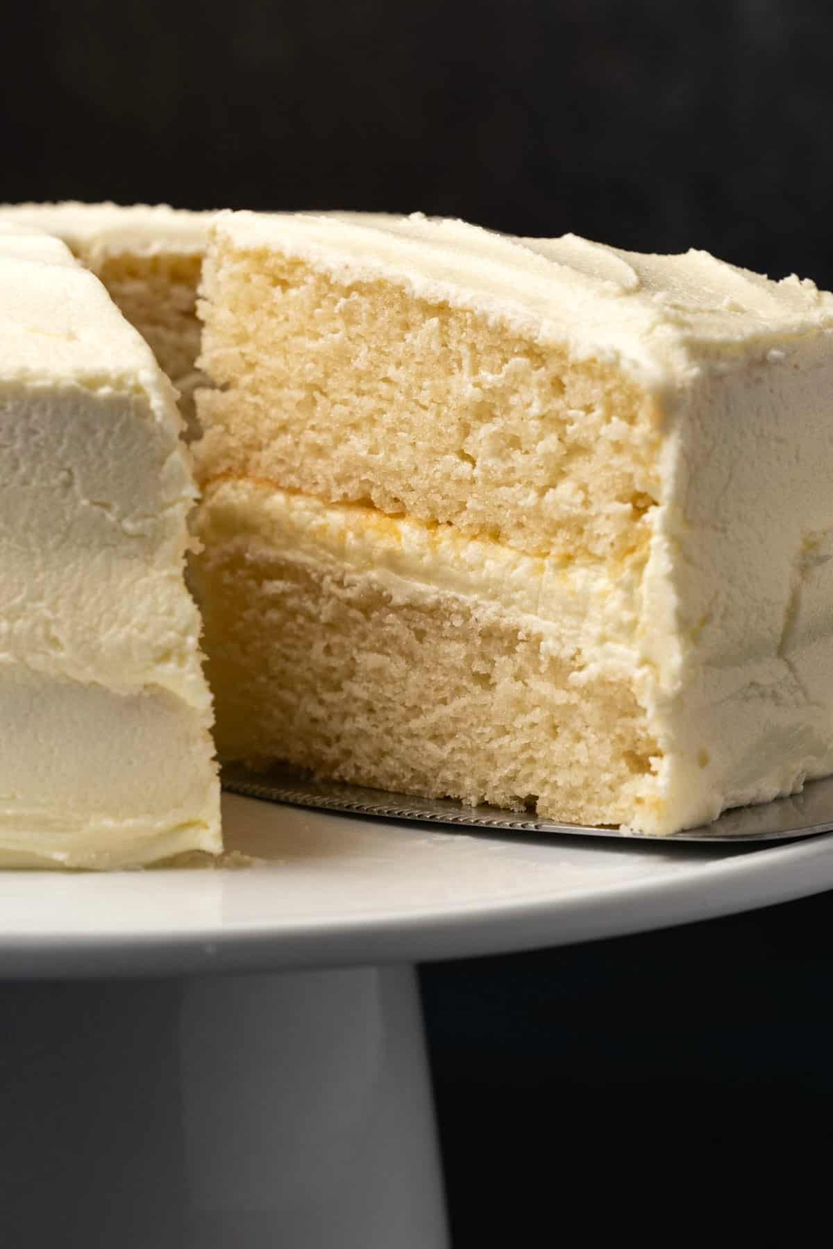 Vegan white cake with one slice cut on a white cake stand.