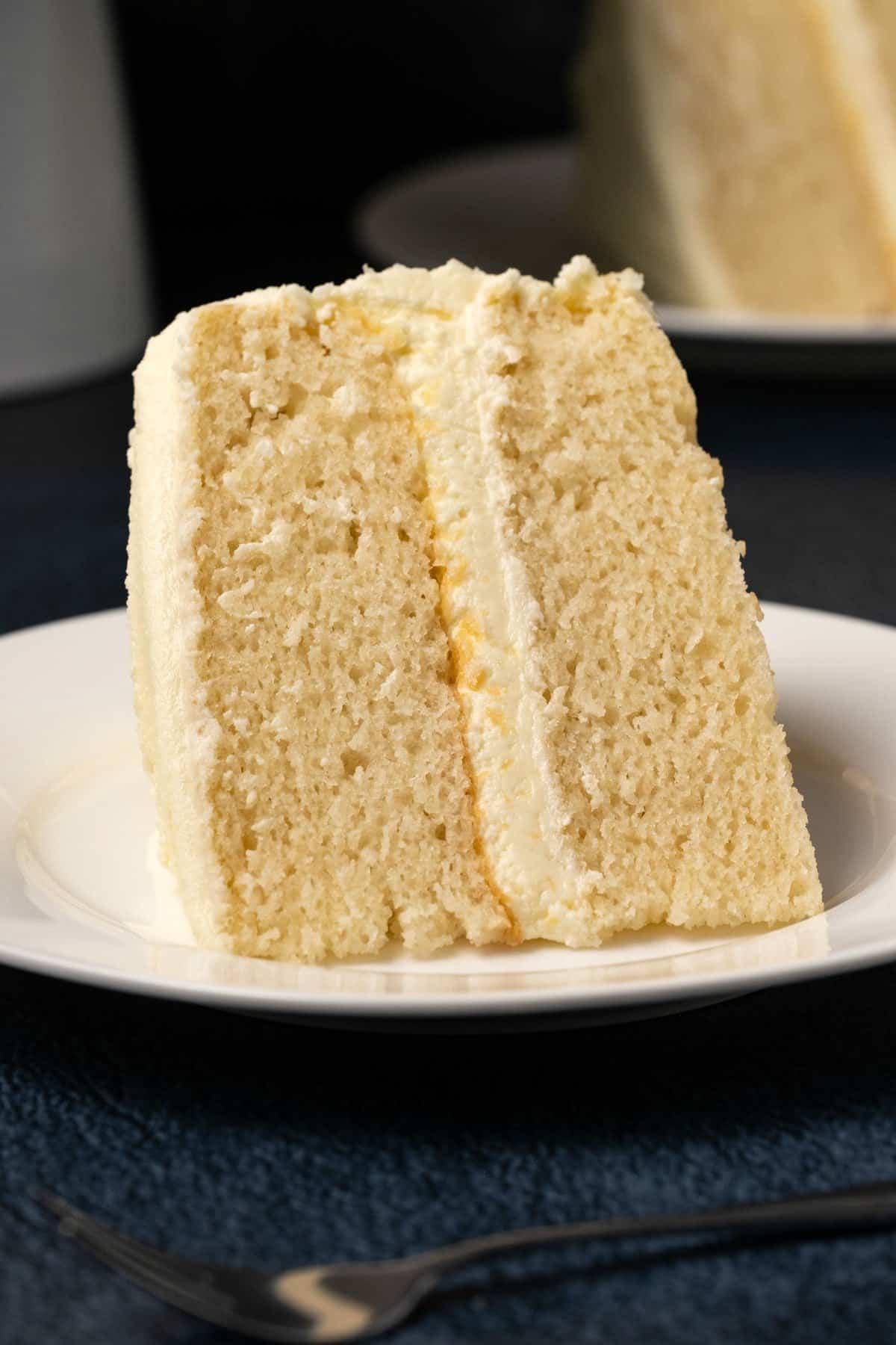 Slice of vegan white cake on a white plate.