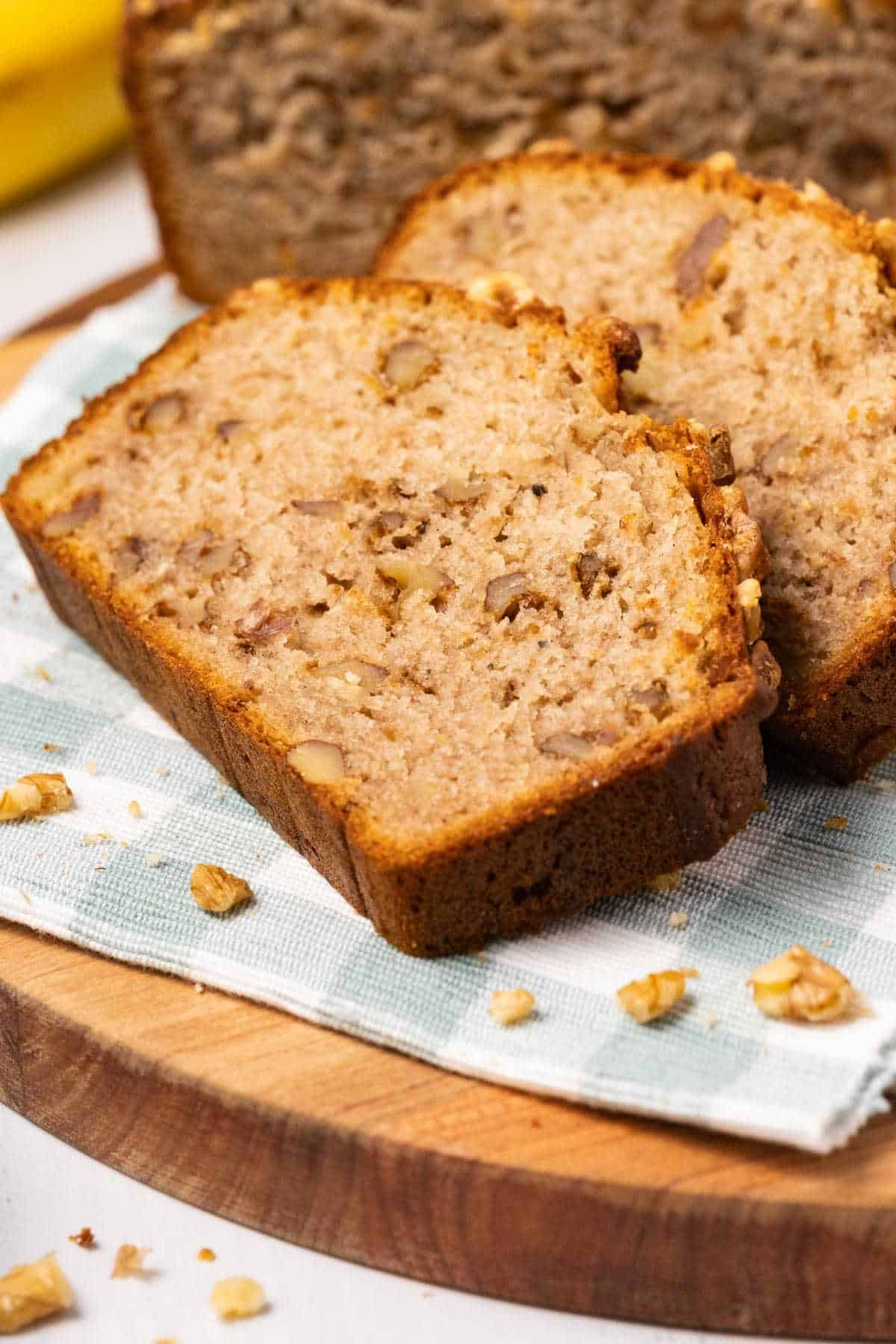 Slices of banana bread on a napkin and wooden board.