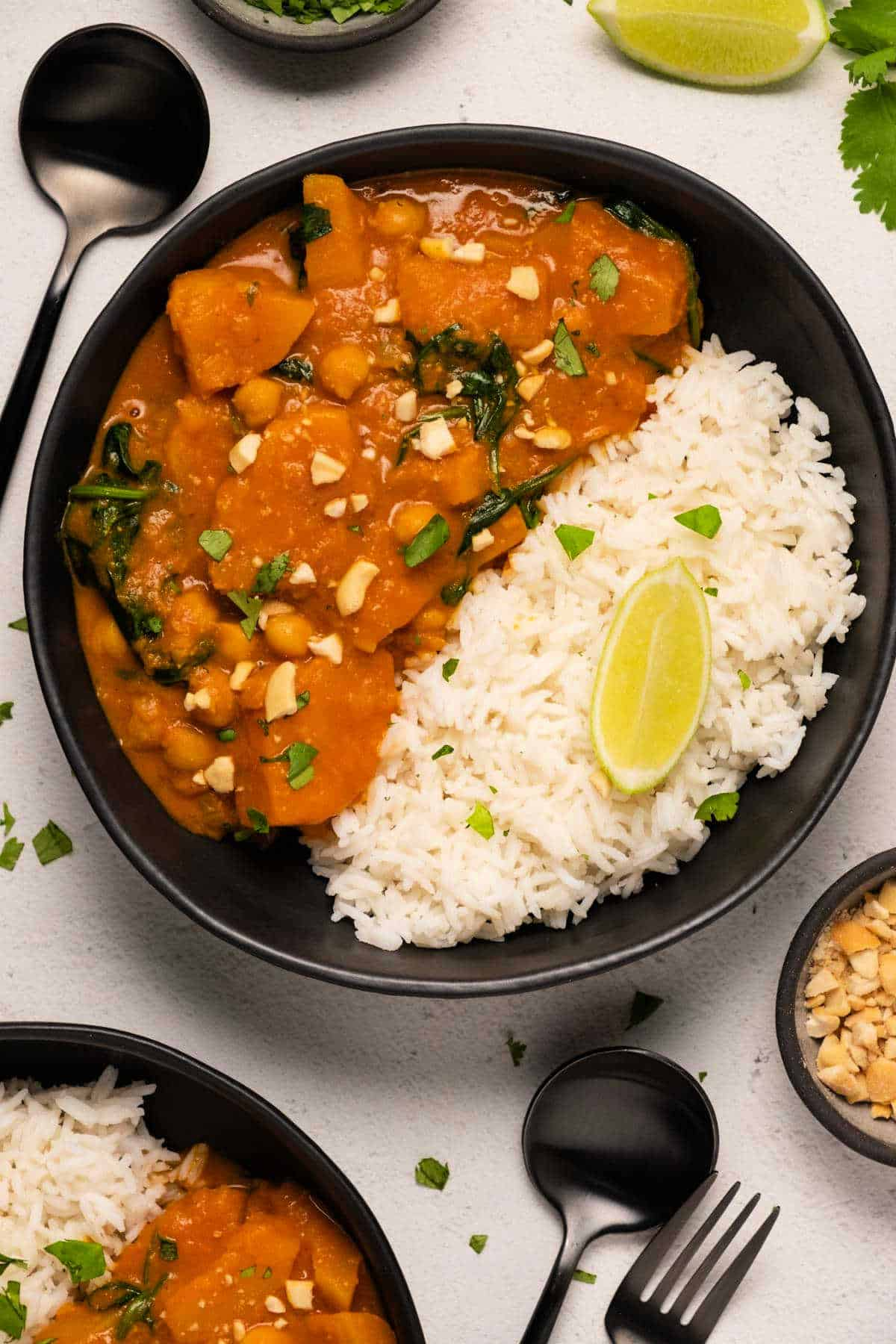 Butternut squash curry with basmati rice and fresh cilantro in a black bowl.