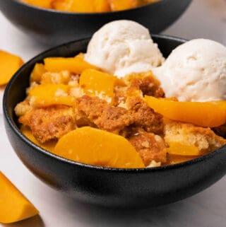Vegan peach cobbler with ice cream in a black bowl.