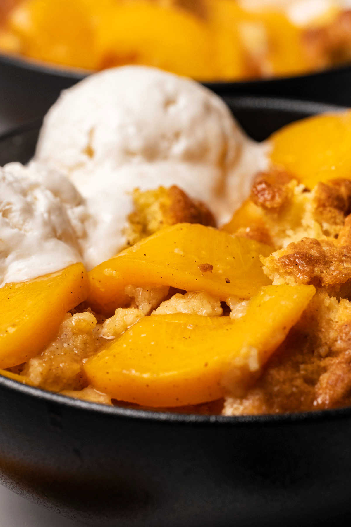 Close up photo of vegan peach cobbler in a black bowl with ice cream.