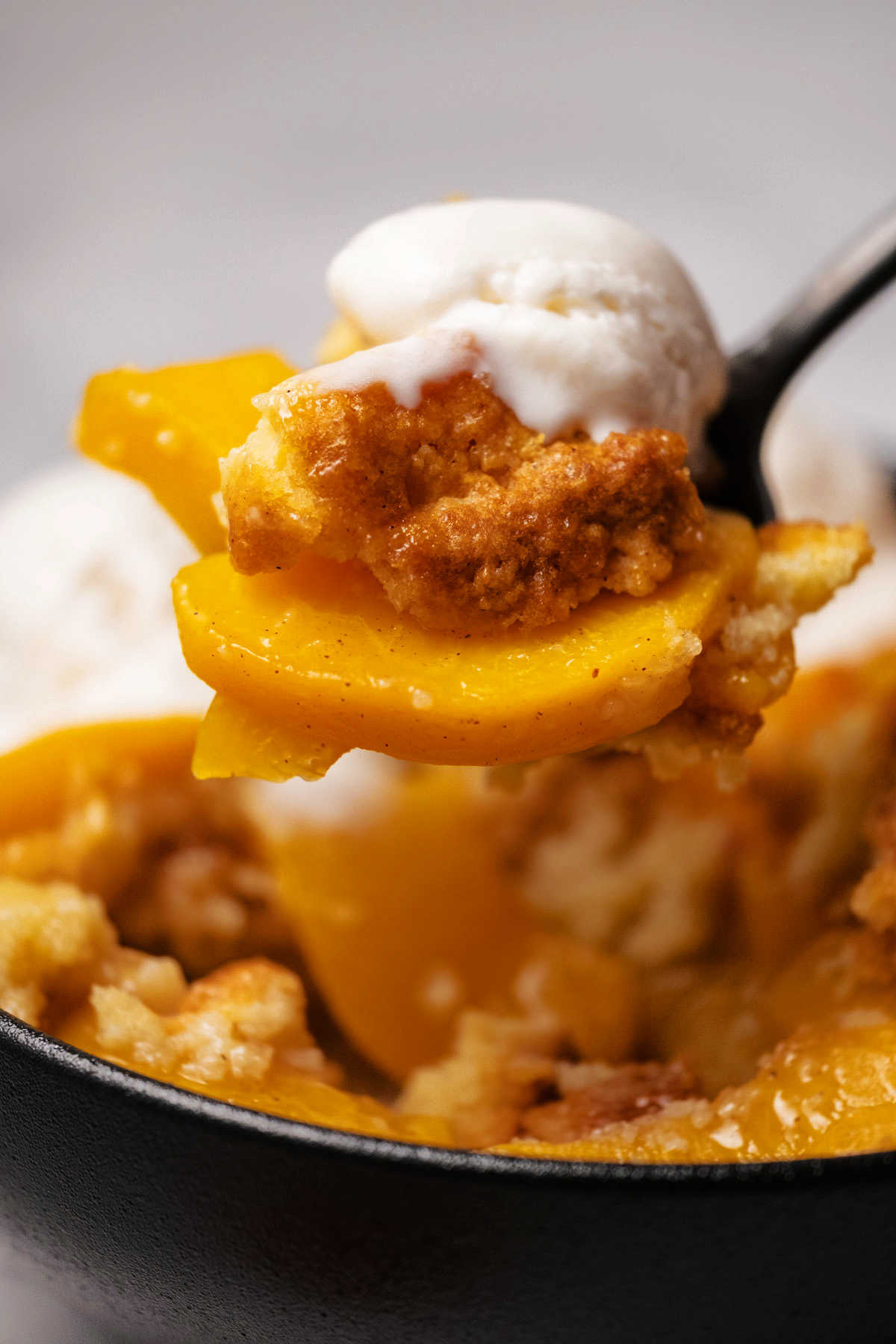 Spoonful of peach cobbler and ice cream.