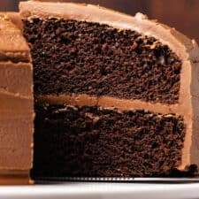 Vegan chocolate cake on a white cake stand.