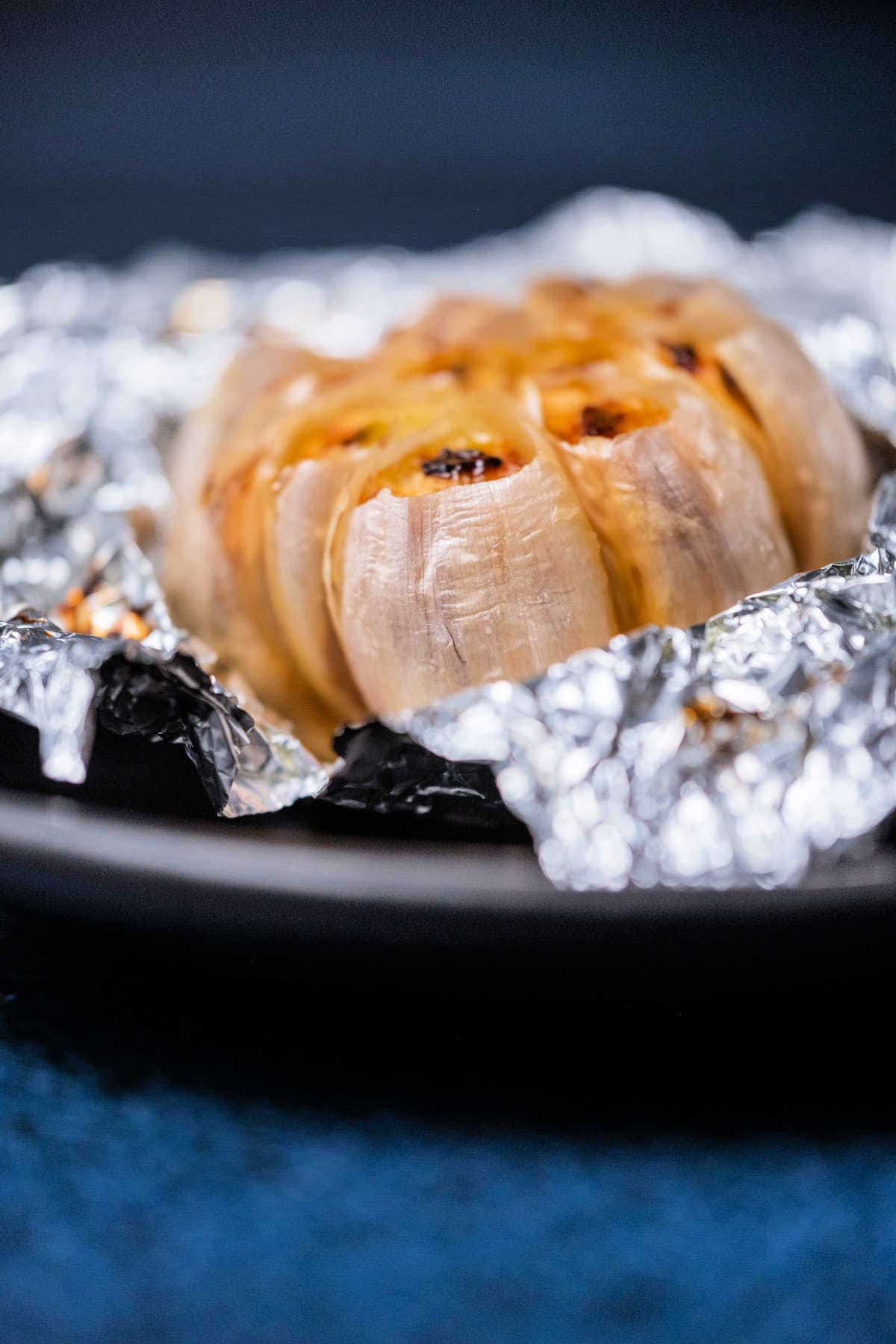 Whole roasted garlic on a black plate.