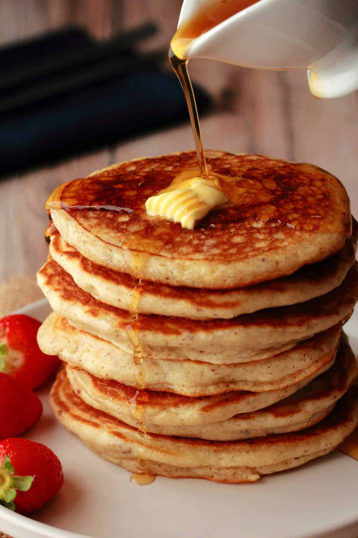 Vegan pancakes in a stack with syrup pouring over them.