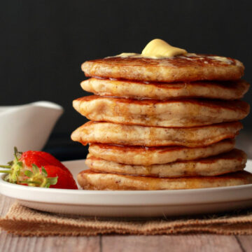 Vegan pancakes stacked up on a plate topped with vegan butter and syrup.