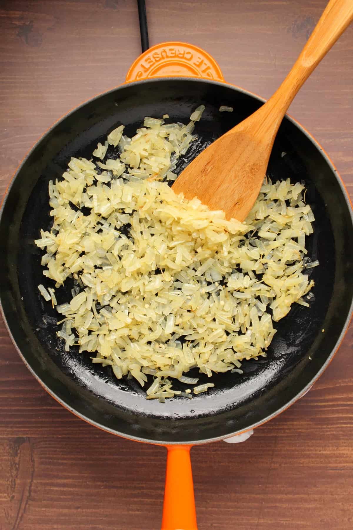 Sautéed onions in a frying pan with a wooden spatula.