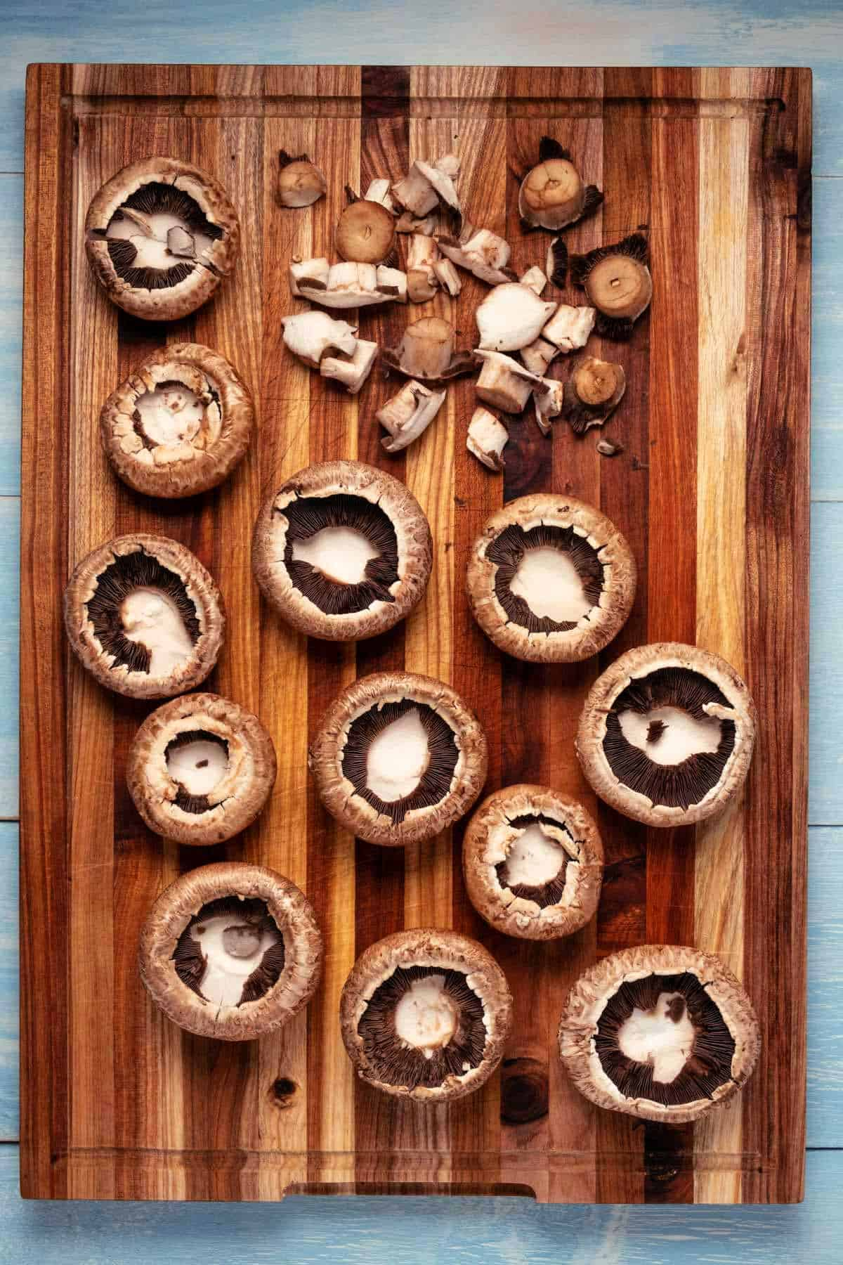 Large mushrooms on a wooden cutting board.
