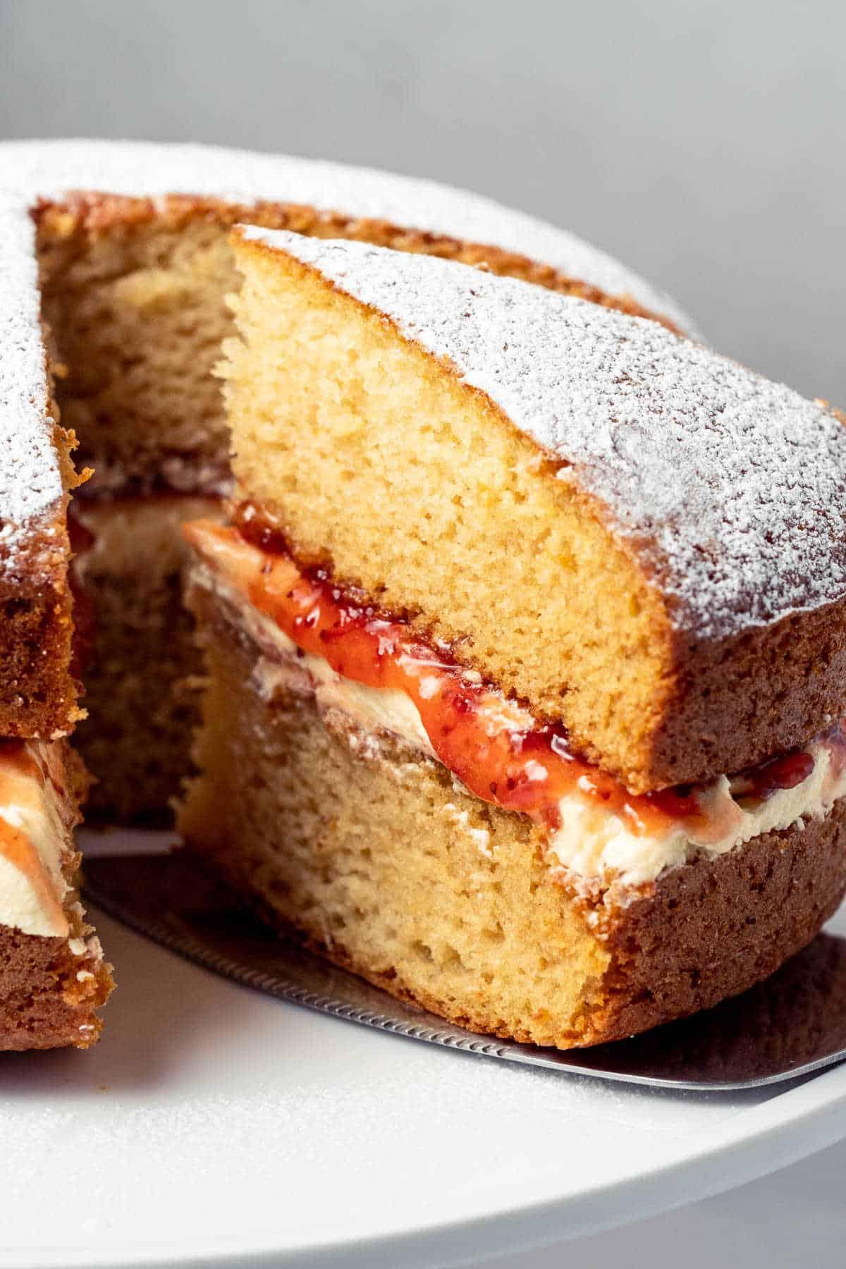 Victoria sponge cake on a white cake stand.
