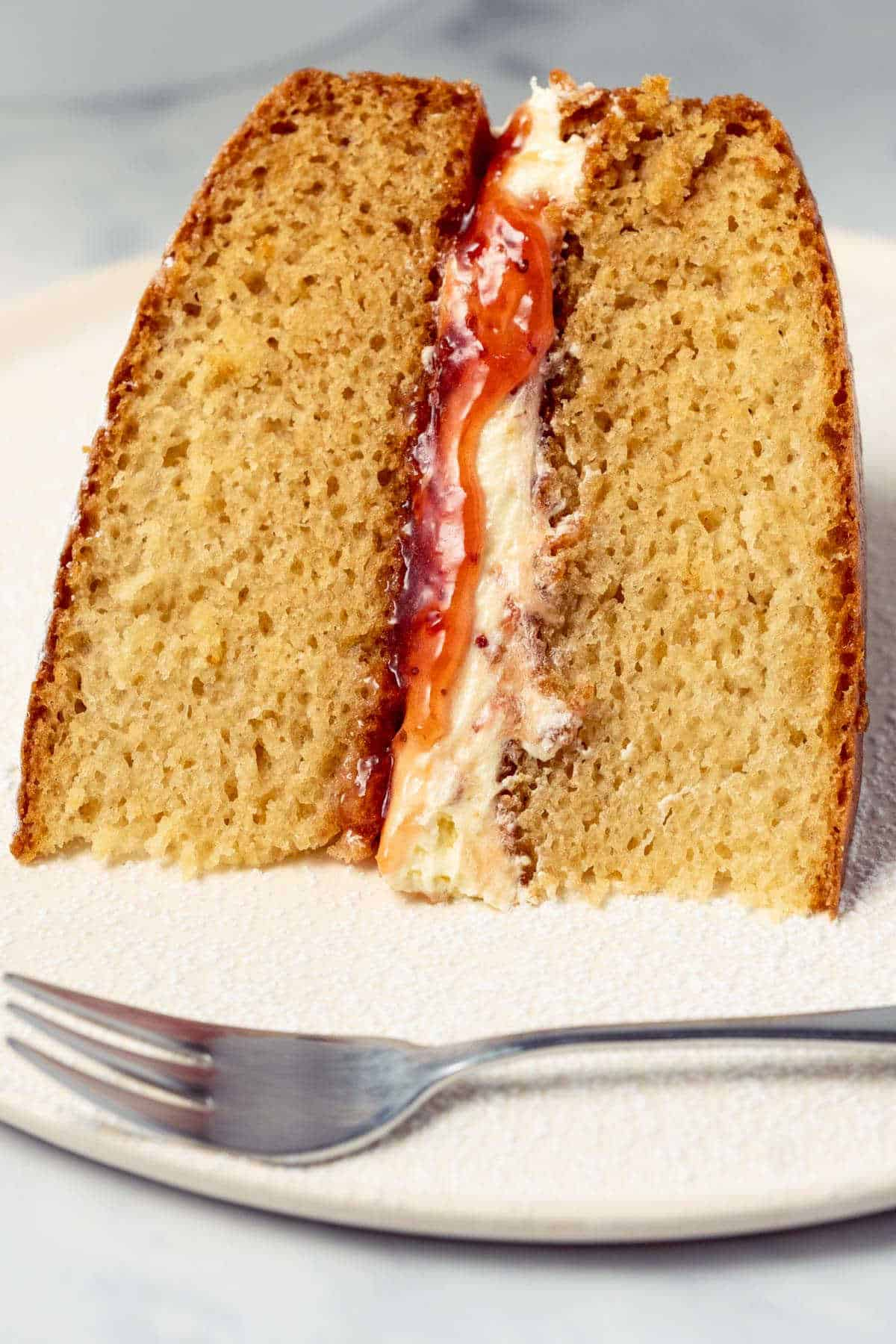Slice of vegan Victoria sponge cake on a white plate.
