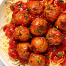 Close up photo of spaghetti, chickpea meatballs and sauce in a white bowl.