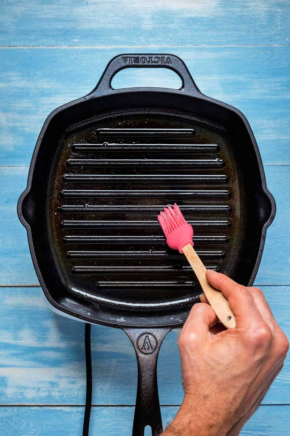 Photo of a grill pan being brushed with grapeseed oil.