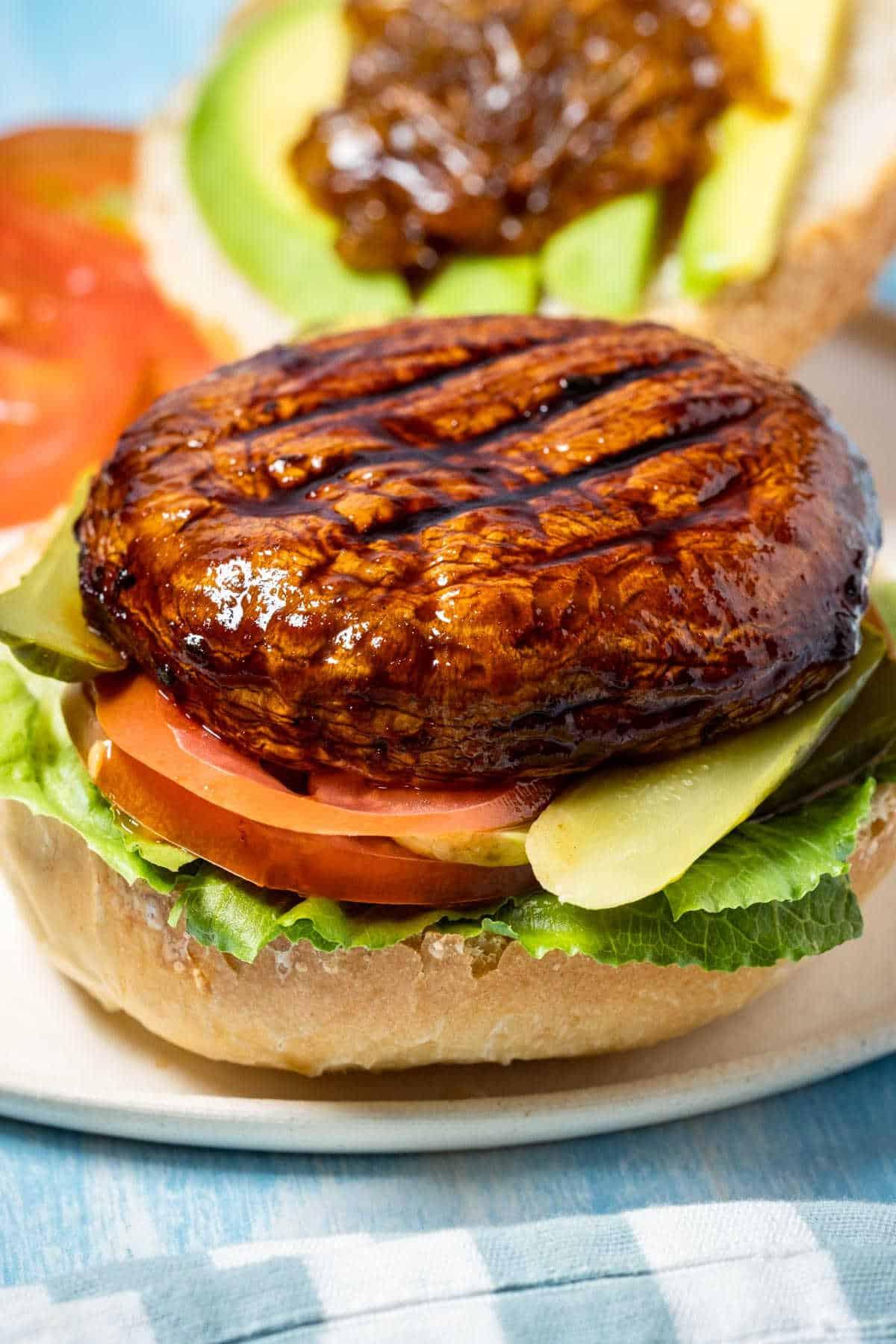 Portobello burger with lettuce, tomato, pickle on a white plate.