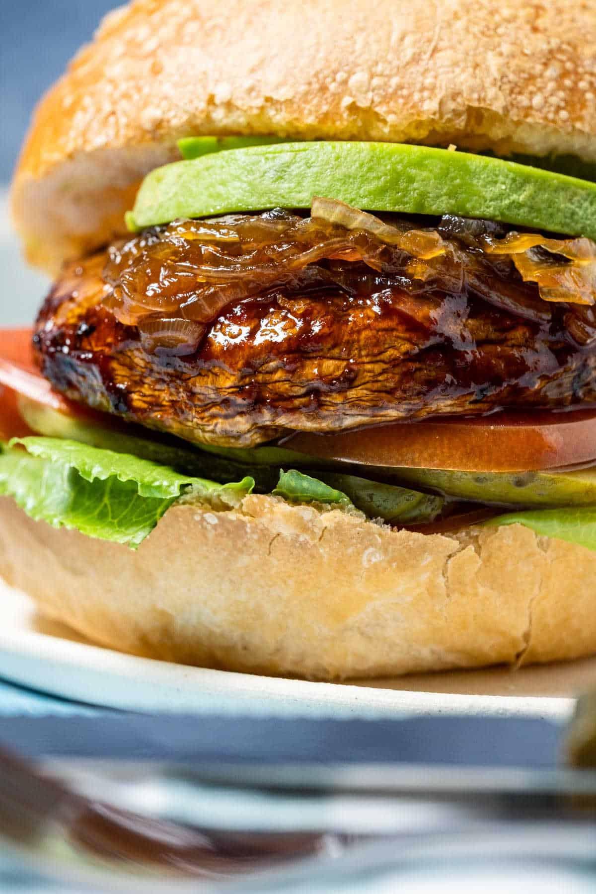 Portobello burger with lettuce, tomato, pickle and avocado on a white plate.