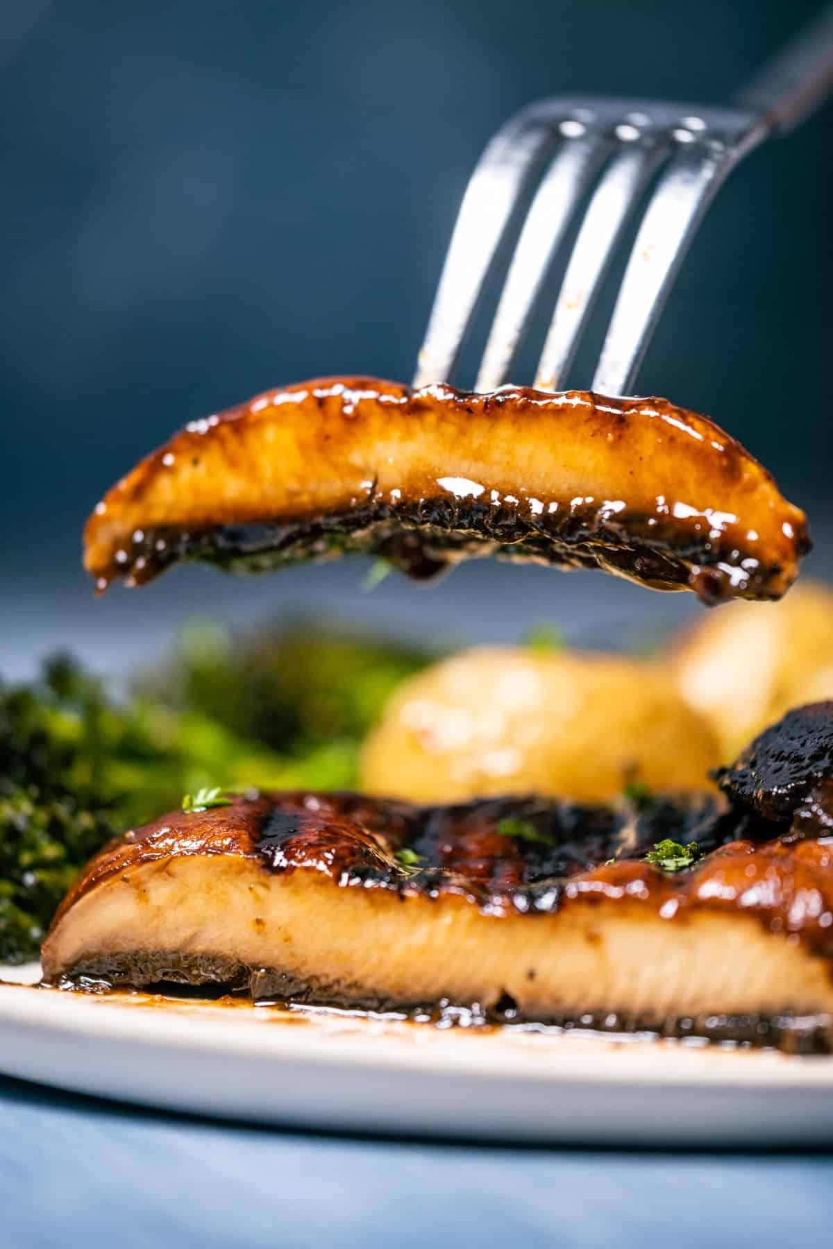 Slice of portobello mushroom steak on a fork.