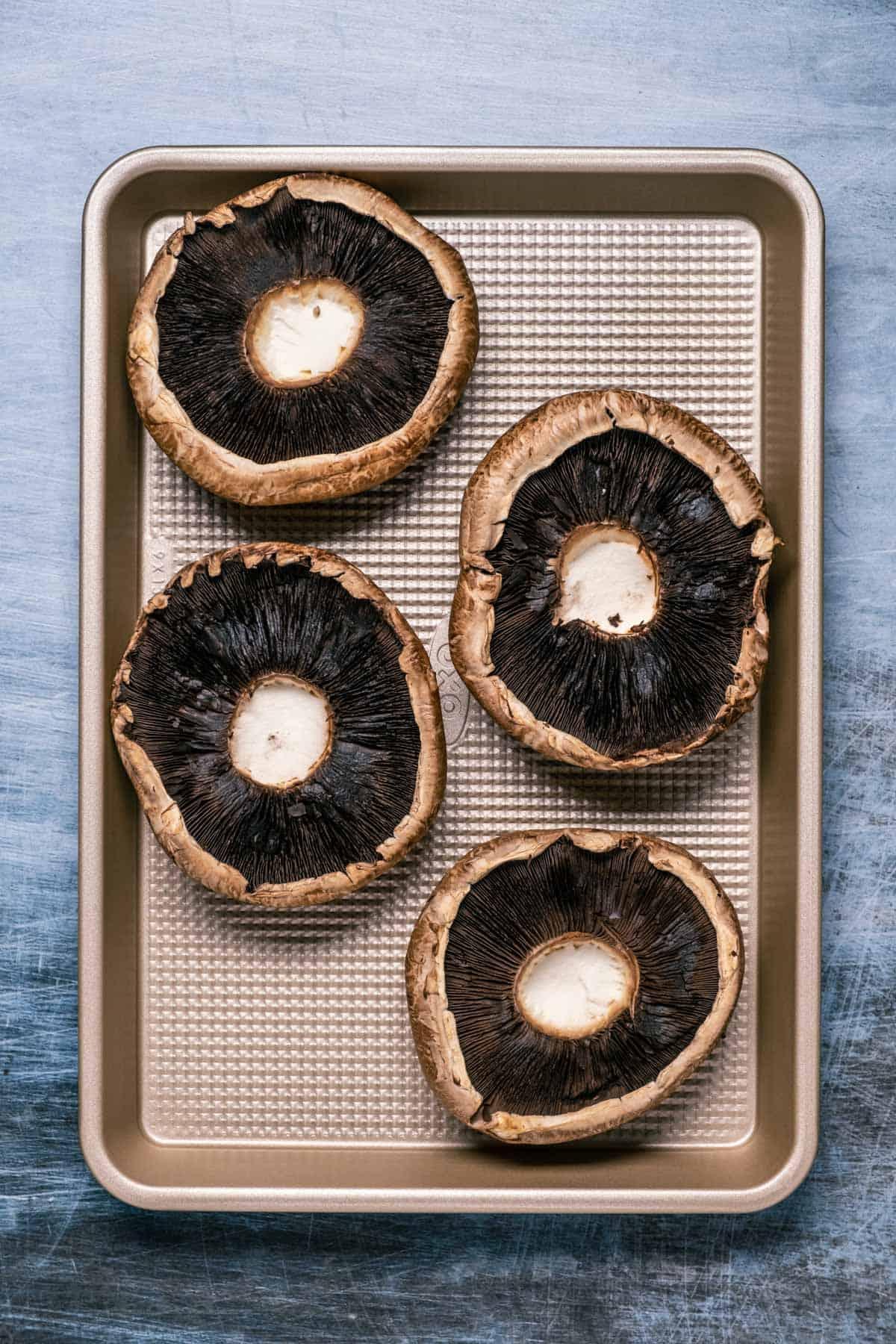 Portobello mushrooms on a baking tray.