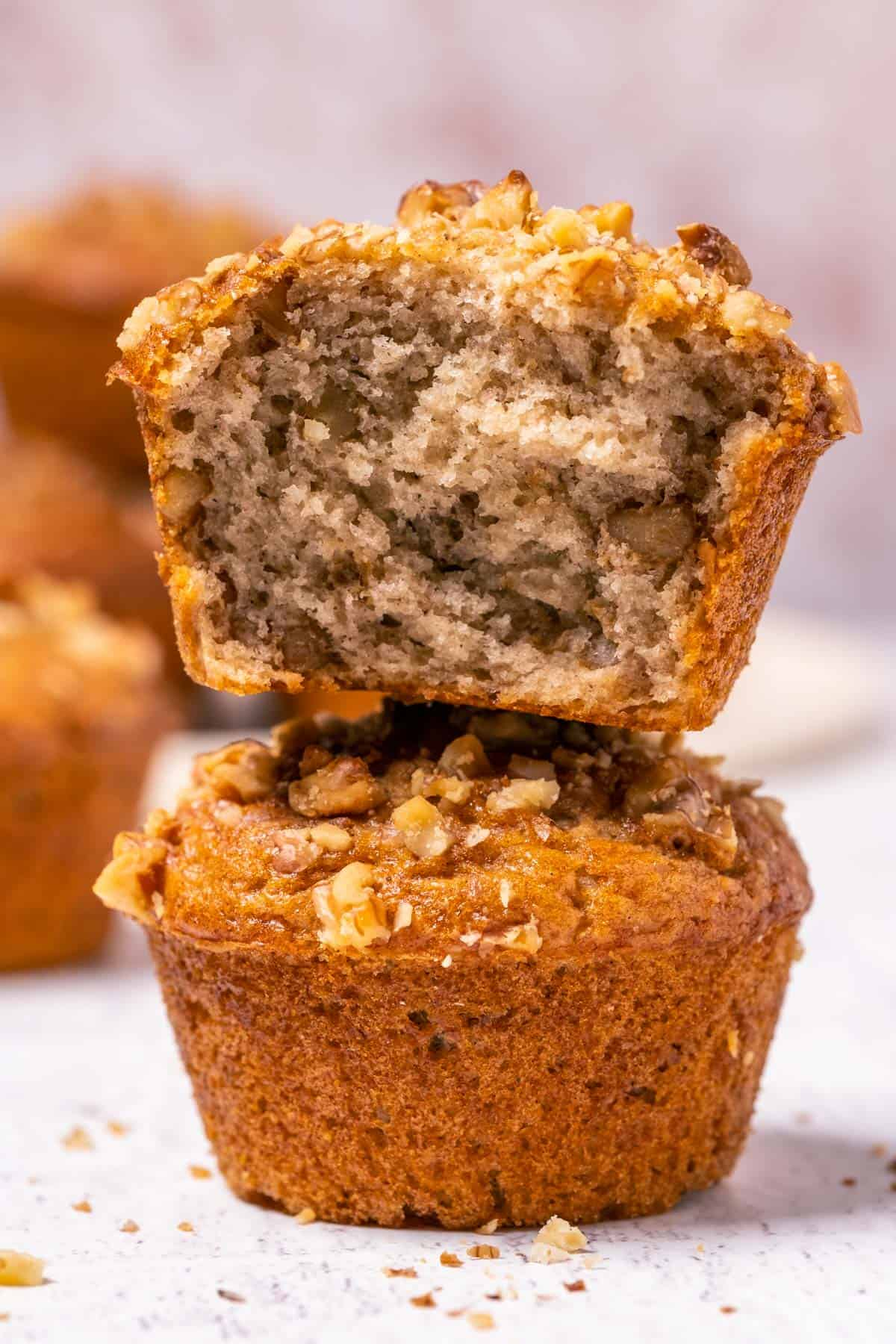 Stack of two vegan banana bread muffins with the top muffin broken in half.
