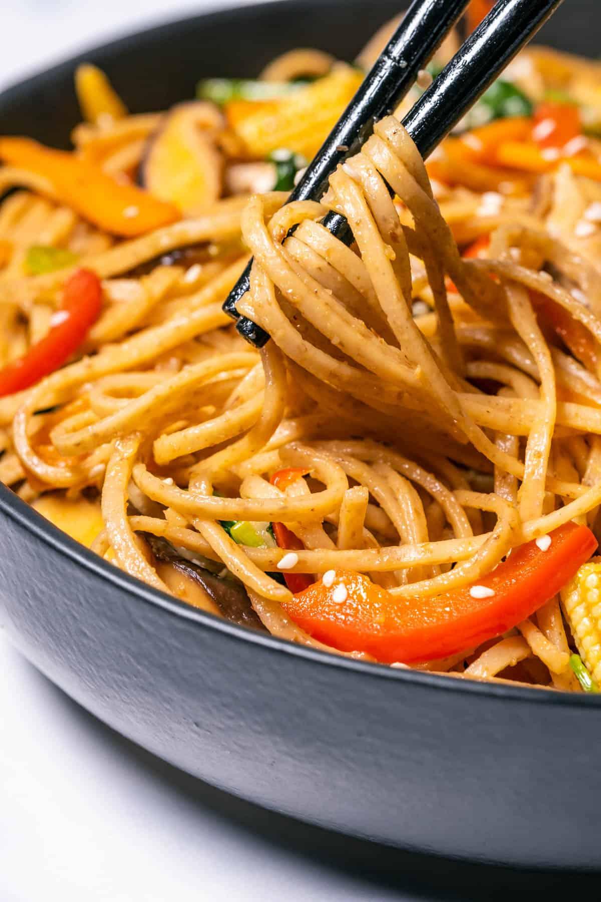 Vegan lo mein in a black bowl with chopsticks.