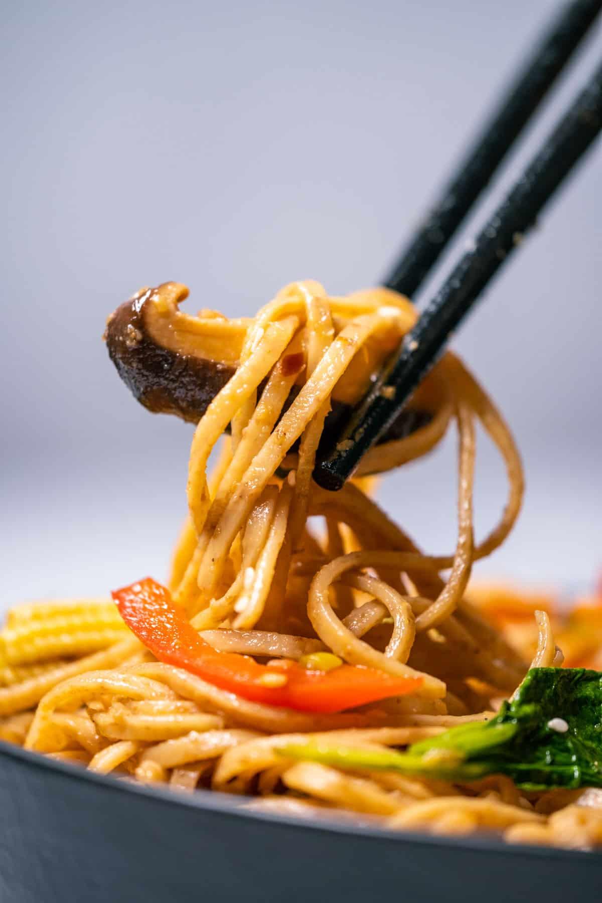 Chopsticks lifting vegan lo mein out of a black bowl.