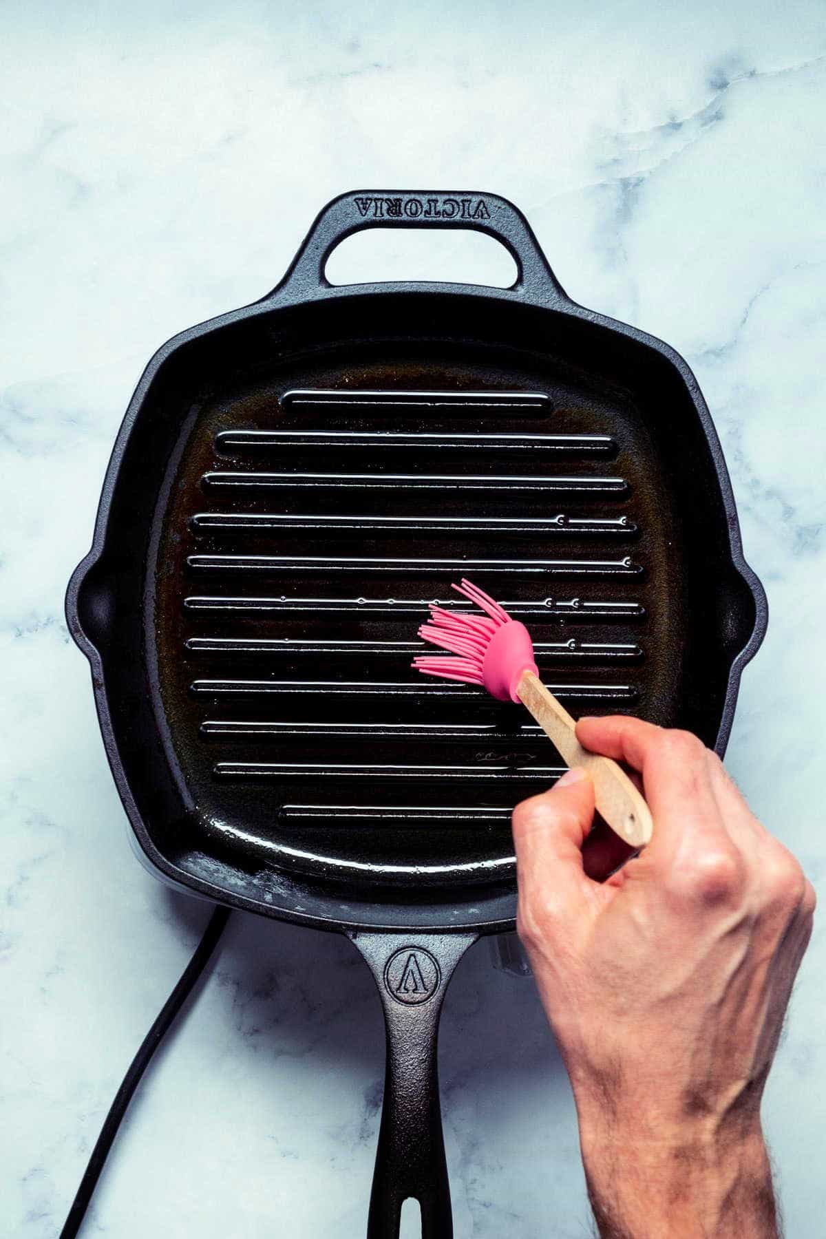 Photo of brushing a grill pan with oil.