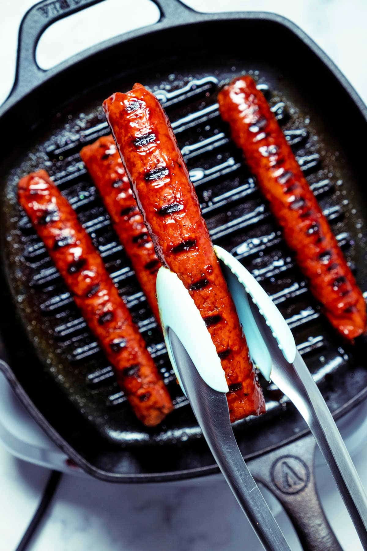 Photo of a sausage being lifted out of a grill pan with tongs.