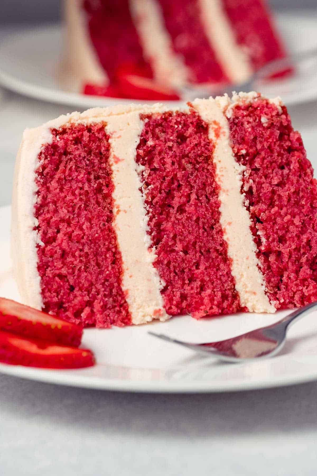 Slice of strawberry cake on a white plate with a cake fork.