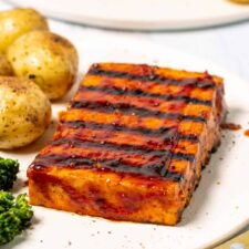 Tofu steak on a white plate with baby potatoes and broccoli.