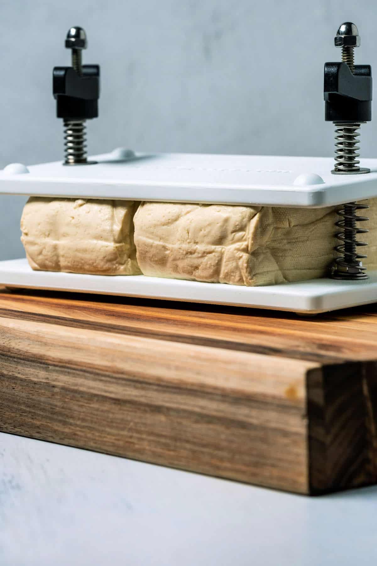 Two blocks of tofu in a tofu press.