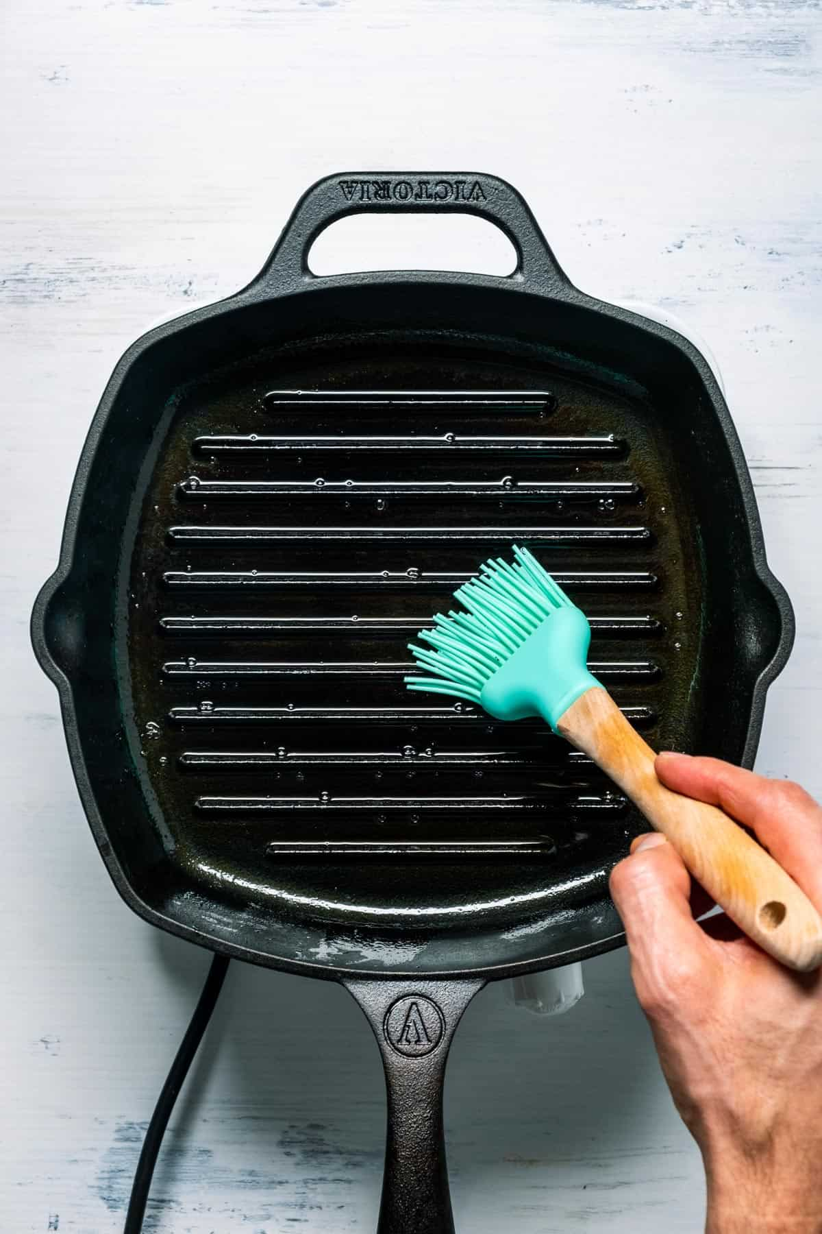 Photo of brushing oil onto a cast iron grill pan