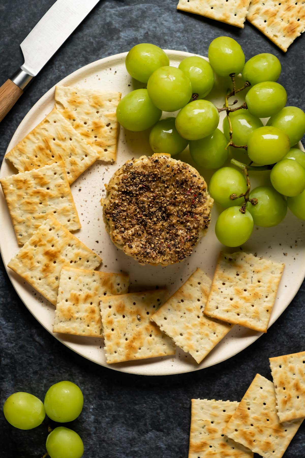 Vegan camembert on a white plate with crackers and grapes.