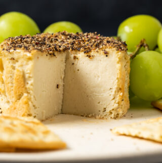 Vegan camembert with slices removed on a white plate with crackers and grapes.