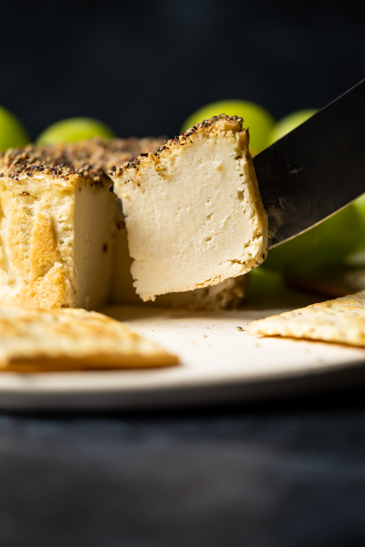 Slice of vegan camembert ready to serve from a white plate with crackers and grapes.