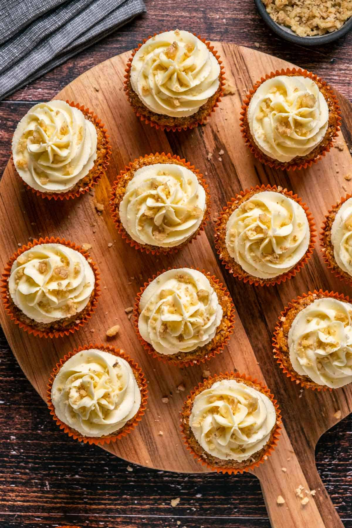 Vegan carrot cake cupcakes on a wooden board.