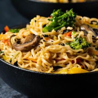 Vegan chow mein in a black bowl.