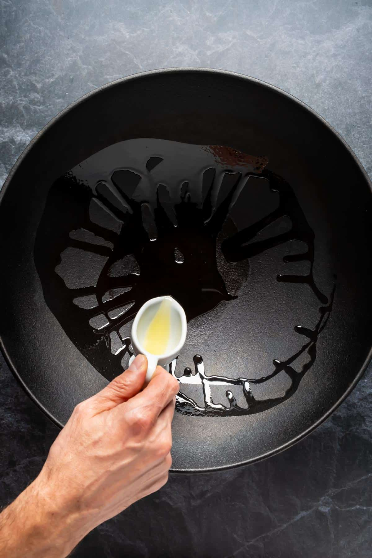 Pouring oil into a large wok.