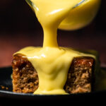 Custard pouring from a glass jug over a slice of sticky toffee pudding.