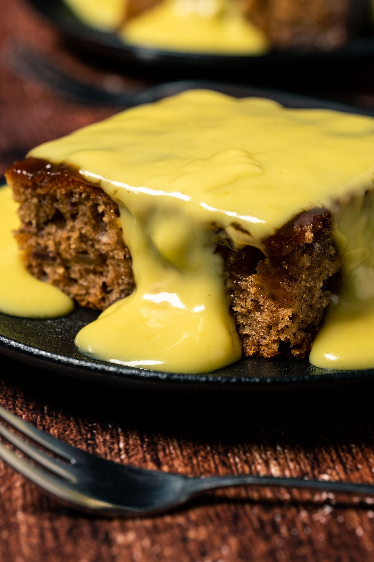 A slice of sticky toffee pudding topped with custard.